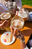 Group of four friends drinking beer. Group of four people in Couple in traditional Bavarian dress, Lederhosen and Dirndl (only parts of body to be seen), in a Royalty Free Stock Images