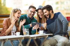Group of four friends having a coffee together. Two women and two men at cafe talking laughing and enjoying their time using digital tablet stock images