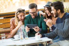 Group of four friends having a coffee together. Two women and two men at cafe talking laughing and enjoying their time using digital tablet stock photography