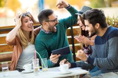 Group of four friends having fun a coffee together. stock photo