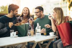 Group of four friends having fun a coffee together Stock Photos