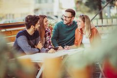 Group of four friends having fun a coffee together. Two women and two men at cafe talking laughing and enjoying their time royalty free stock photo