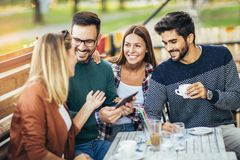 Group of four friends having fun a coffee together. Two women and two men at cafe talking laughing and enjoying their time royalty free stock images