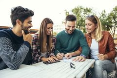 Group of four friends having fun a coffee together. Stock Images