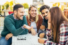 Group of four friends having fun a coffee together. Royalty Free Stock Images