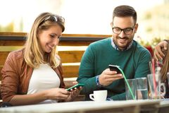 Group of four friends having fun a coffee together. Two women and two men at cafe talking laughing and enjoying their time. Using phone stock images