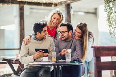 Group of four friends having fun a coffee together. Two women and two men at cafe talking laughing and using digital tablet royalty free stock photography