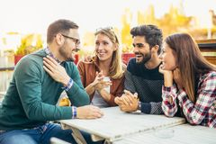 Group of four friends having fun a coffee together. Stock Photography