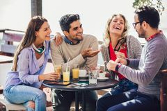 Group of four friends having fun a coffee together. Two women and two men at cafe talking laughing and enjoying their time stock images