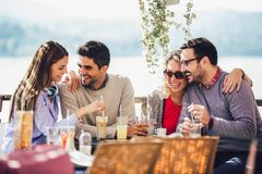Group of four friends having fun a coffee together. Two women and two men at cafe talking laughing and enjoying their time stock photography