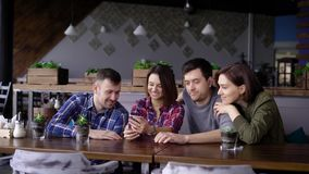 Group of four friends sitting at the restaurant together and using digital gadget. Two handsome men and two smiling. Group of four friends are sitting at the stock video