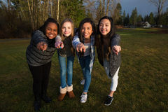 Group of four girls pointing fingers and smiling Stock Photography