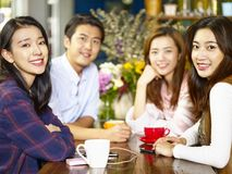 Happy young asian adults looking at camera smiling in coffee sho. Group of four happy asian young adults men and women looking at camera smiling while gathering Royalty Free Stock Photo