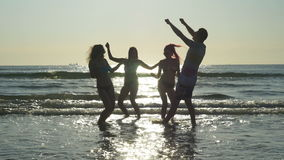 Group of four happy friends dancing on the shore of the sea stock video