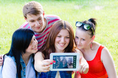 Group of four happy smilng young people friends taking picture of themselves with tablet Stock Photos