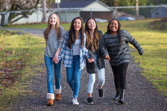 Group of four happy young girls laughing while walking on trail Royalty Free Stock Photography