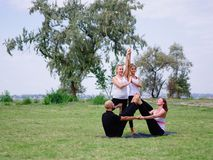 A group of four holds yoga classes in the park. Healthy lifestyle. stock image