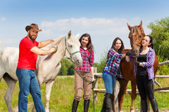 Group of four horseback riders with their horses. Four horseback riders having rest with their horses, standing next to the fence of the paddock at sunny day Royalty Free Stock Photo