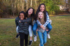 Group of four kids playing and giving piggyback rides Royalty Free Stock Images