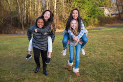 Group of four kids playing and giving piggyback rides Royalty Free Stock Image
