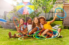 Four kids in a group sit with hula hoops on lawn