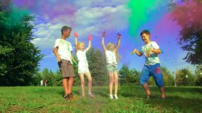 Group of four kids: two boys and two girls enjoying a sunny day on green meadow and throwing holy powder up to the air stock footage