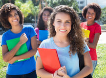 Group of four latin and caucasian female students. Outdoor in the city in summer Stock Photography