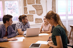 Group of four millenials in meeting. Group of four millenials in a meeting, one lady taking notes with her tablet next to her and the others talking in the Stock Photo