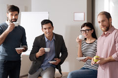 Group of four people drinking coffee while their break. We are happy. Delighted young office workers having break standing next to each other while looking Royalty Free Stock Images