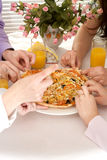 Group of four people with pizza and juice Stock Image