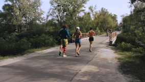 Group of four people running in the park at sunrise stock footage