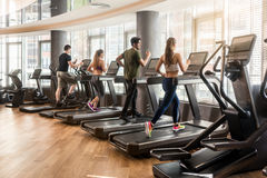 Group of four people running on treadmills in fitness gym stock photo