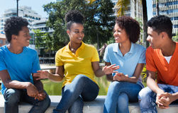 Group of four speaking latin american young adult outdoor. In the summer in the city royalty free stock photography