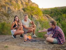 Camping students near bonfire on a natural background. Cute couples eating marshmallows. Picnic day concept. Copy space. A group of four students relaxing on a stock photos