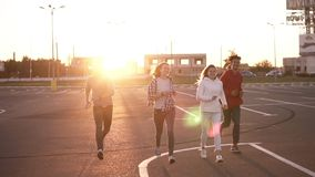 Group of four stylish friends are running by empty parking zone outdoors - fun happiness, young men and women are stock footage