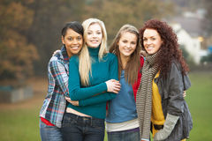 Group Of Four Teenage Girls In Autumn Landscape. Smiling at camera Royalty Free Stock Images