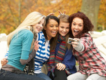 Group Of Four Teenage Girls Taking Picture. With Camera Sitting On Bench In Autumn Park Stock Image