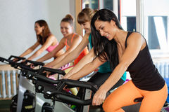 Group of four women in the gym cycling Stock Photography