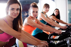 Group of four women in the gym cycling Stock Photos