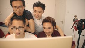 Young asian musician editing music using computer. Group of four young asian musician working together editing music using desktop computer stock video footage