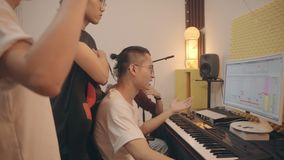 Young asian musicians working together editing music. Group of four young asian musician working together editing music using desktop computer stock footage