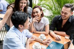Group of four young Asian people sitting together outdoors at a stock images