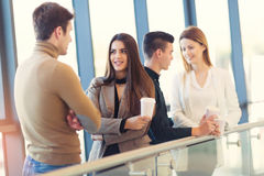 Group of four young business people on a coffee break Stock Image
