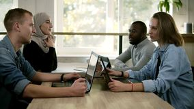 Group of four young mixed race and cultural people - muslim woman, african man and two caucasians have a meeting stock video footage