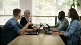 Group of four young mixed race and cultural people - muslim woman, african man and two caucasians have a meeting stock footage