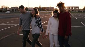 Group of four young multirace friends laughing while walking outdoors. Young men and women enjoying a summer day at stock video footage
