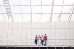 Group of four young smiling people wearing stylish casual clothing looking at camera standing in light office or university. Group of four young smiling people royalty free stock photography