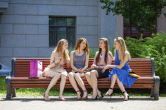 Group Of Four Young Women Sitting On Bench In summer Park Royalty Free Stock Images
