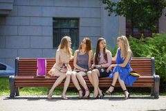 Group Of Four Young Women Sitting On Bench In summer Park Royalty Free Stock Photography
