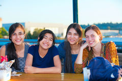 Group of four young women smiling together by lake Stock Image